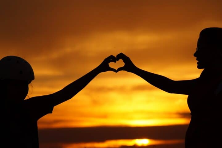 Heart connection between two people at sunset