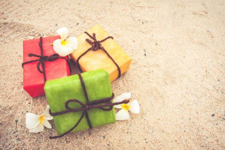 Three cute wrapped gifts sitting on the sand